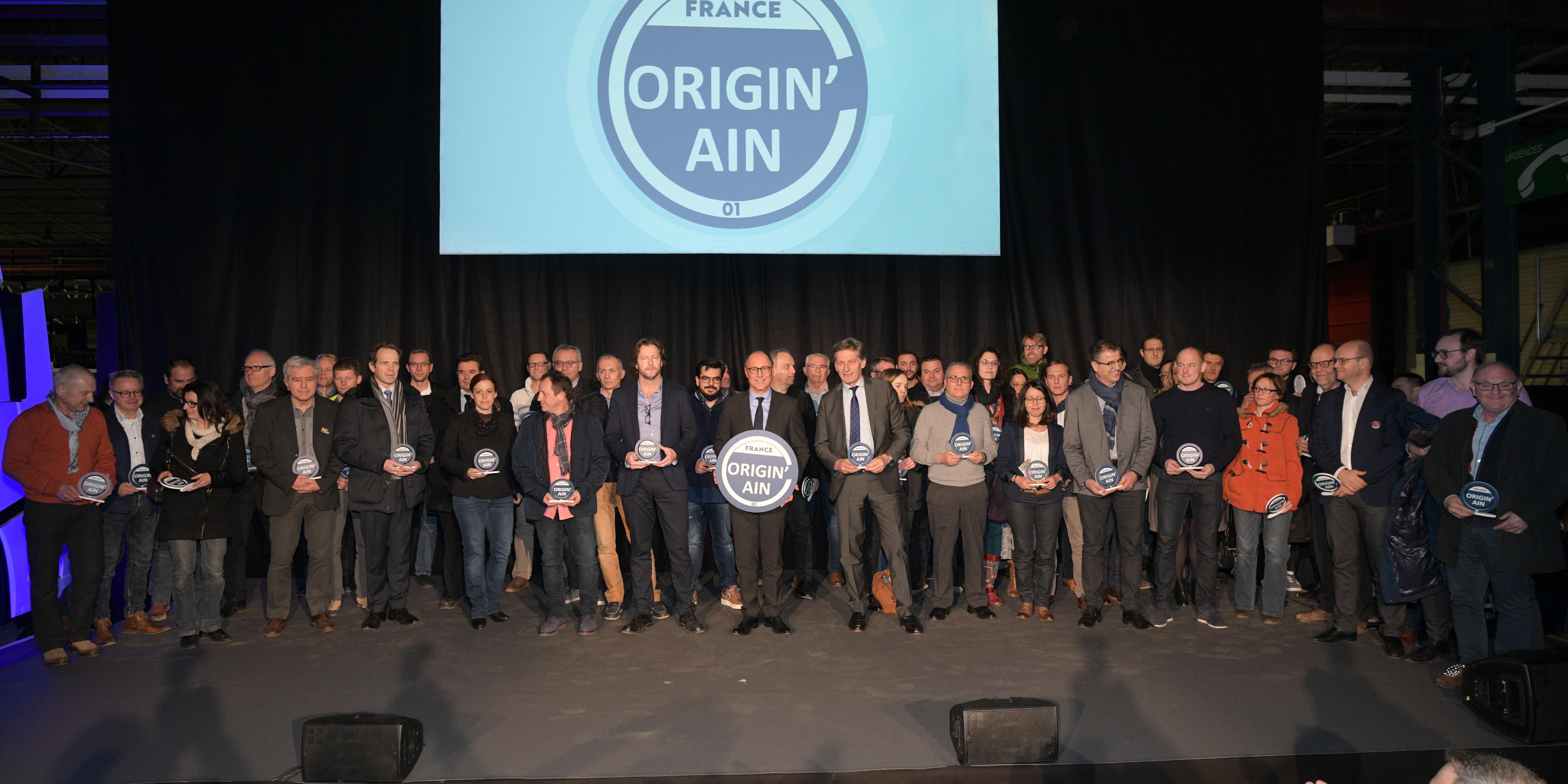 Un groupe de 65 représentants d'entreprises de l'Ain entoure le Président Jean Deguerry sur une scène