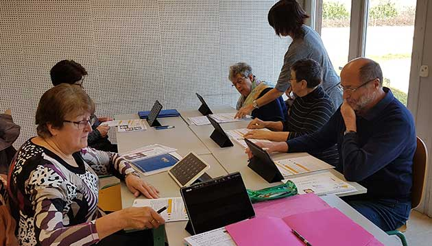 un groupe de séniors assis autour d'une table avec chacun une tablette dans le cadre d'un atelier sur le numérique