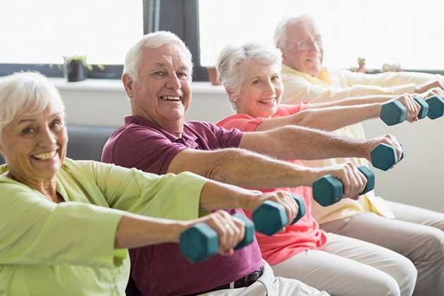 Groupe de seniors souriant pratiquant un exercice physique à base d'althère en mousse.