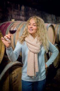 Jeune femme oeunologue inspecte la couleur et la robe d'un verre de vin rouge du bugey AOC dans le caveau Bonnard