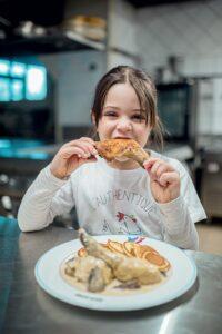 Jeune fille qui mord à pleine dent une cuisse de poulet de bresse au Restaurant La Table Bagesienne à Bâgé le Châtel.